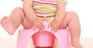 10 months baby girl on potty isolated on white